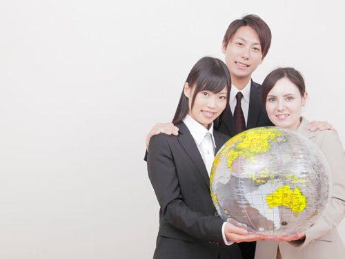 地球儀を持つ外国人女性と日本人の男女